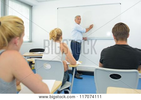 Teacher writing on white board in front of class