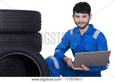 Mechanic With Laptop And Tires