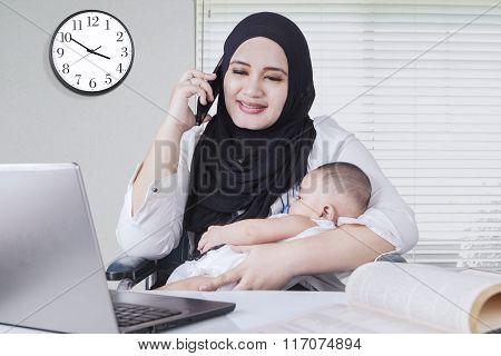 Muslim Woman Nursing Her Baby While Working