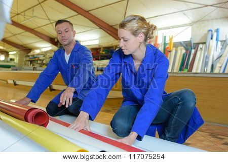Man and woman looking at rolls of material