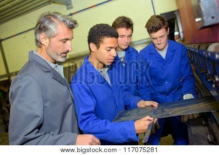 Apprentice measuring a piece of flat metal