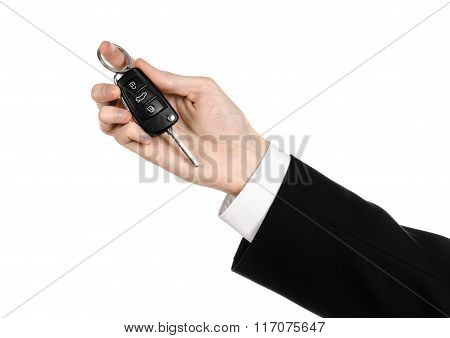 Business Theme: Car Salesman In A Black Suit Holding A Car Key Isolated On White Background