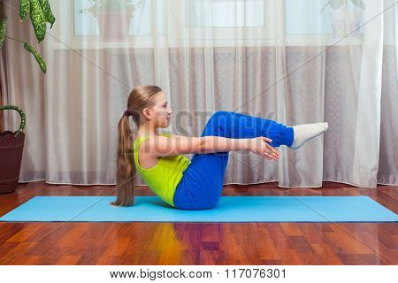 fitness. sport, training and lifestyle concept - Child doing exercises on mat in home.