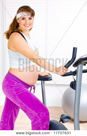 Smiling beautiful pregnant woman preparing for workout on static bicycle