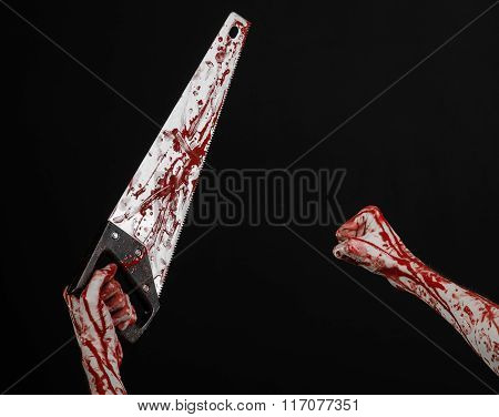 Halloween Theme: Bloody Hand Holding A Bloody Saw On A Black Background