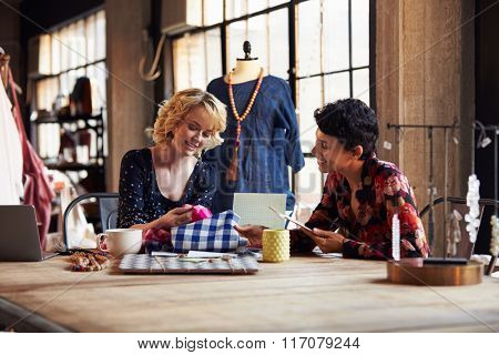 Two Female Fashion Designers In Meeting Discussing Textiles