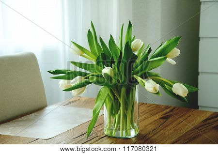 Bunch of white tulips in a glass vase
