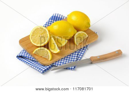 whole and sliced lemons on wooden cutting board and checkered dishtowel