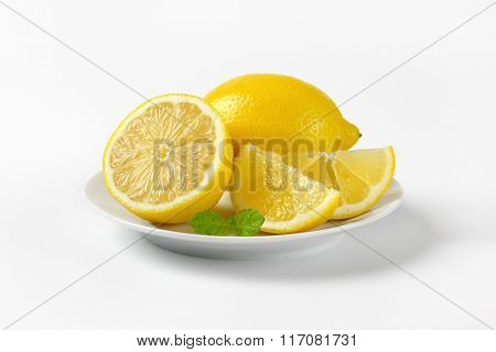 plate of whole and sliced lemons on white background