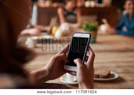 Close Up Of Woman Using Mobile Phone In cafe