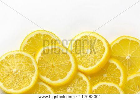 heap of fresh lemon slices on white background