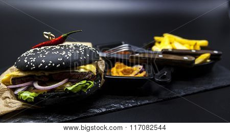 Set of black burger. Stone plate with: black burger roll slices of juicy marble beef, fused cheese, fresh salad with French fries on a cast-iron griddle, with chili sauce and guakomole.