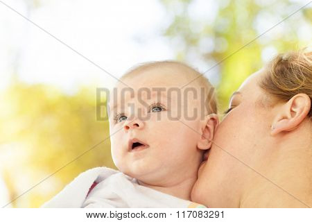 Portrait of loving mother hugging her baby outdoors