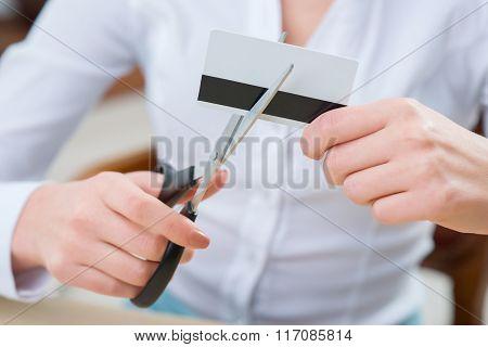 Pleasant woman cutting credit card