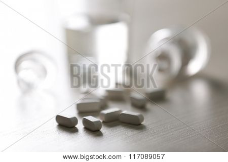 Red capsules spilled from pill bottle and glass of water on the table, close up