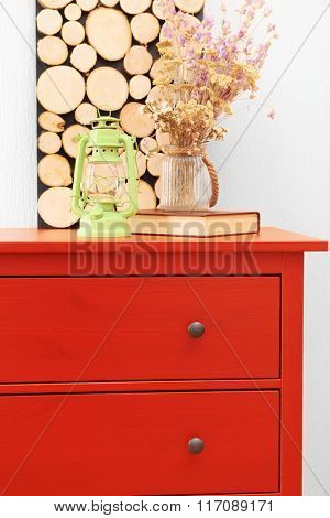 Room interior with red wooden commode, flowers and lantern on light wall background