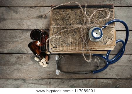 Stack of books, pills and stethoscope on wooden table, top view