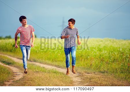 Happy Male Couple Running Through The Summer Field