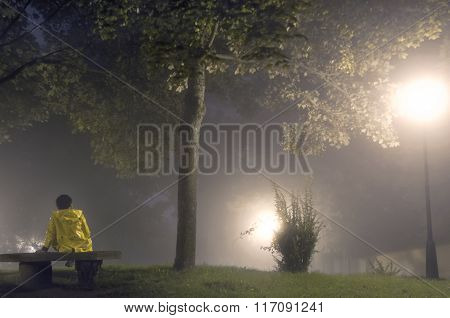 Woman sitting on a bench at night a foggy day