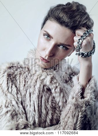 Beauty portrait of a young white woman in fur with chain, look strict to camera
