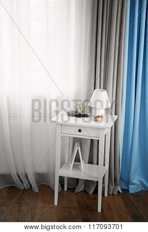 Small white table with lamp on curtain background
