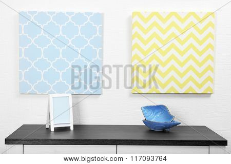 Photo frame and decorations on table with pictures in light room