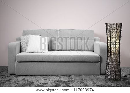 Grey comfortable sofa and modern lamp against white wall in the room