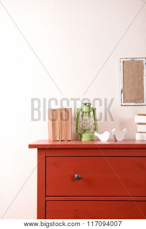 Room interior with red wooden commode, lantern and books on light wall background