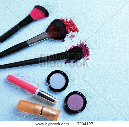 Makeup tools and cosmetics on blue background