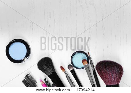 Makeup tools and eye shadows on a light wooden table