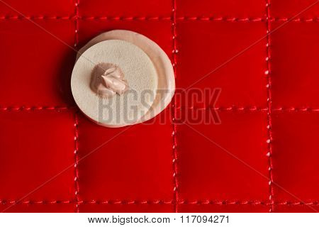 Makeup sponge with liquid foundation on abstract background