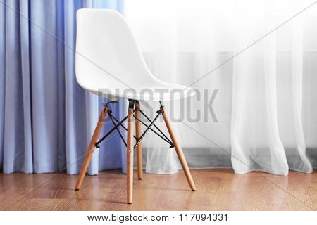 Chair in the room near the window with curtains