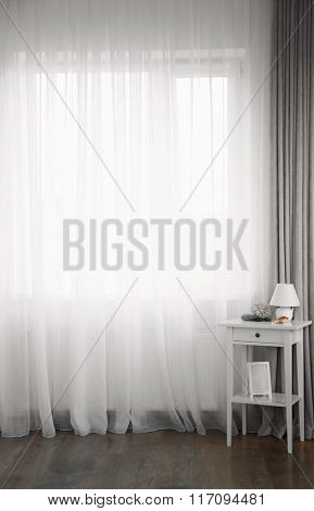 Small white table with lamp and frame on curtain background