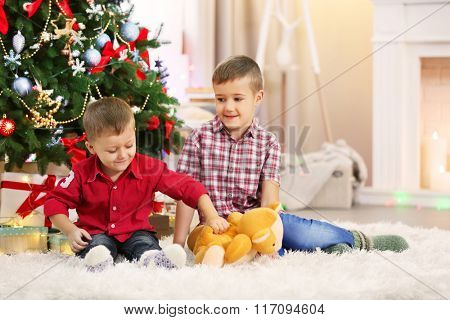Two cute small brothers with teddy bear on Christmas tree background