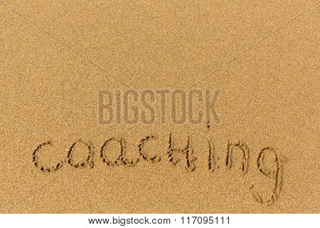 Coaching - word drawn on the sand beach. Background, texture of the sand.