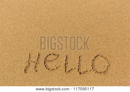 Hello - word drawn on the sand beach. Background, texture of the sand.