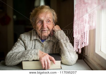 An elderly woman sits with a big book near the window.