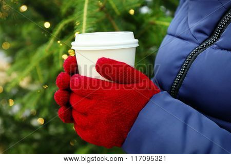 Female hands in mittens with cup of coffee closeup