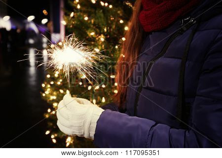 Woman's hand holding Bengal light on Christmas background