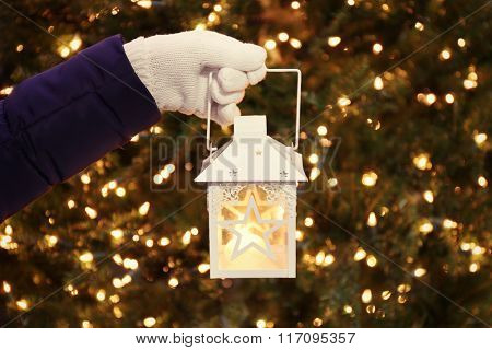 Female hand holding white lantern on lighted background