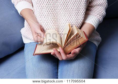 Woman  reading book at home, close up
