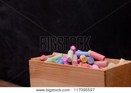 Wooden box of coloured chalk in front of blackboard