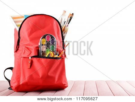 Red backpack full of stationery on wooden table against white background