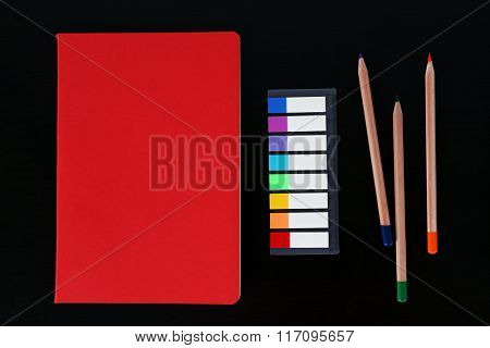 Notebook with coloured pencils and ruler on black table