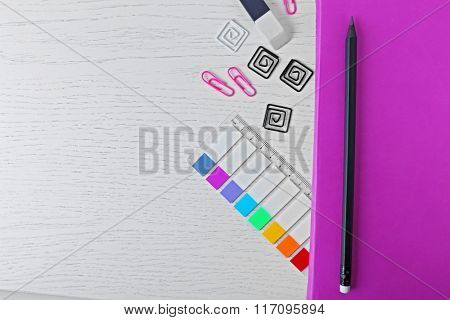 Notebook with stationery on a white table