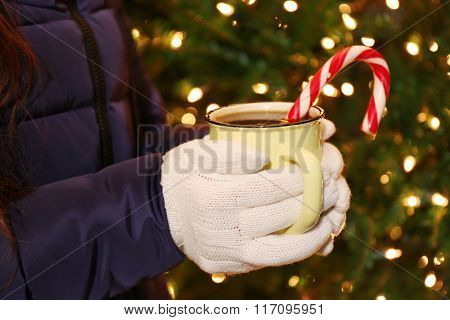 Girl holding a cup of mulled wine with Christmas candy cane on lighted background