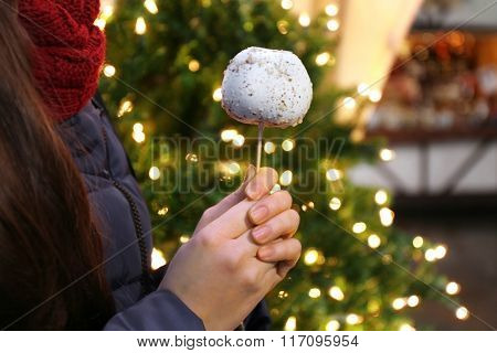 Girl holding delicious white candy apple on a stick