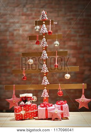 A handmade Christmas tree and presents on wall background