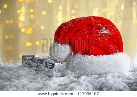 Santa Claus hat with gift boxes on a snowy table over glitter background
