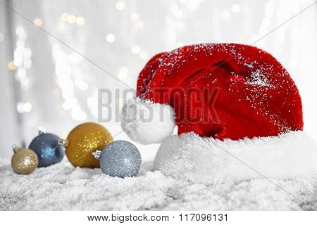 Santa Claus hat with baubles on a snowy table over glitter background